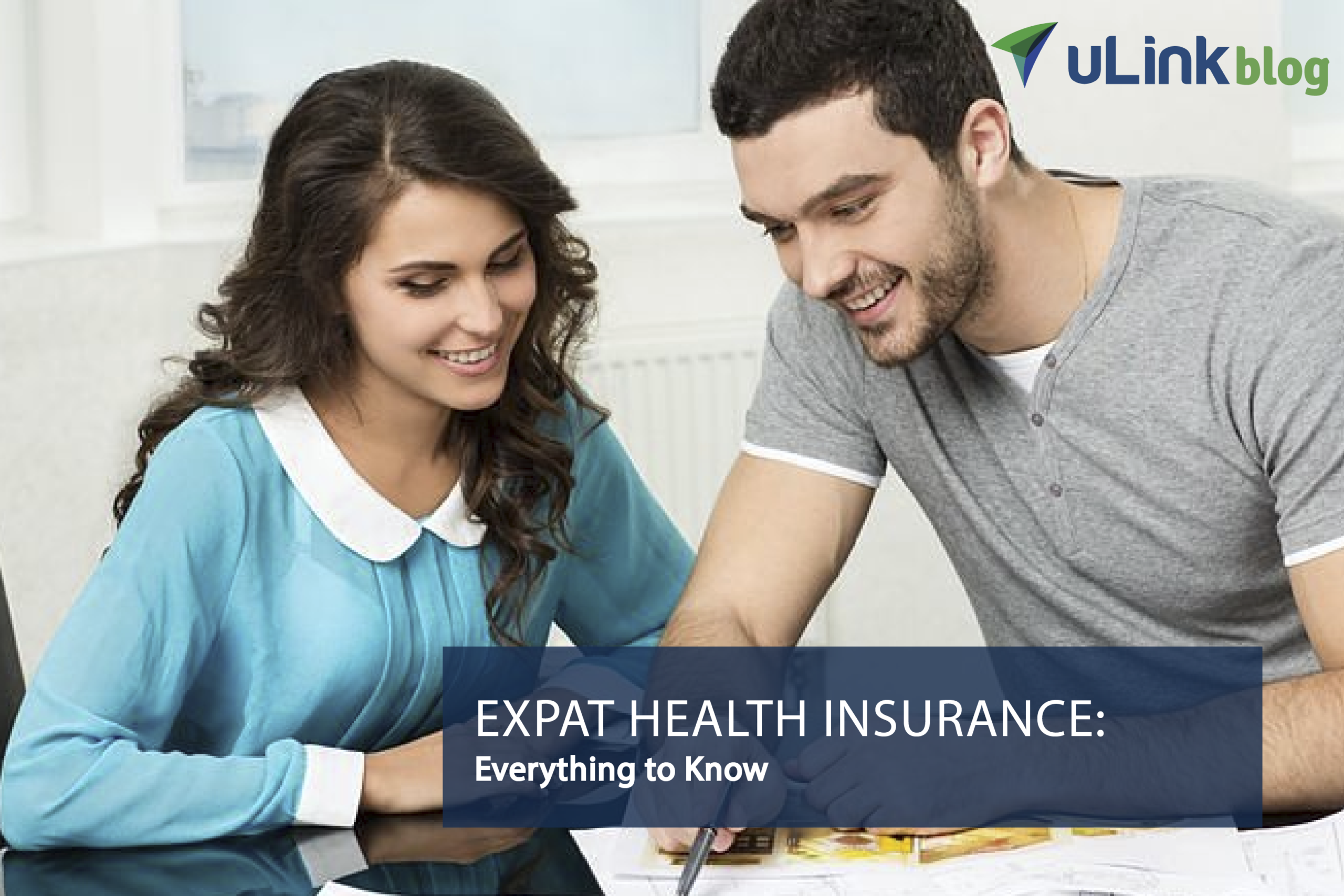 Expat couple sitting at a desk discussing expat health insurance